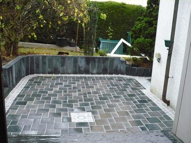 Terrasse mit Pallisaden und Graniteinfassung Betonpflaster